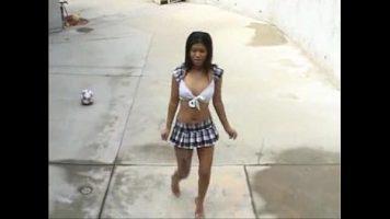 امرأة آسيوية ناضجة تمشي عارية في الفناء في تنورة قصيرة