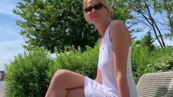 أم شقراء طويلة ترتدي ملابس خفيفة للغاية وتجلس على مقعد في الحديقة