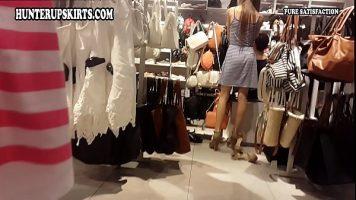 أثناء التسوق ، يتم تصوير امرأة شابة وهي تحاول ارتداء الملابس ولكن الكاميرا الخاصة بها مطوية تحتها