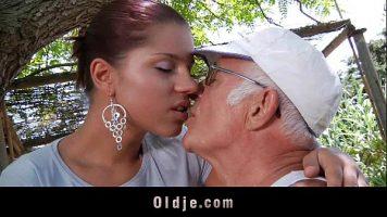رجل عجوز بشعر أبيض يدفع لامرأة شابة ذات ثديين جميلين لترقص أمامها عارية